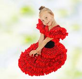 Little girl in a red dress .