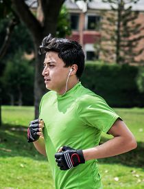 stock photo of track home  - Young man at a local park jogging near home vertical pic - JPG