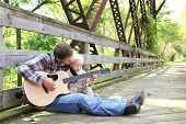 image of fall day  - A father and his young child are sitting outside on a bridge at a park playing guitar together on an autumn day - JPG