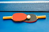 image of ping pong  - Two table tennis or ping pong rackets and ball on a blue table with net - JPG