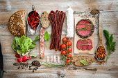 stock photo of salami  - Wholemeal bread with dried salami  and vegetables on a wooden rustic table - JPG