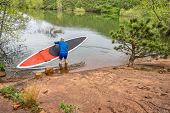 foto of horsetooth reservoir  - senior paddler launching  red SUP paddleboard on a rocky shore of a lake  - JPG