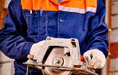 stock photo of millwright  - Hands of man  builder holding circular saw - JPG