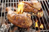 foto of flame-grilled  - Grilled chicken thigh over flames on a barbecue - JPG