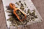 image of peppercorns  - Green peppercorns in wooden scoop on burlap - JPG