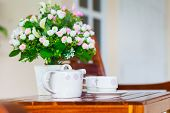picture of teapot  - White porcelain set for tea or coffee and vase of artificial flowers on wooden table at home exterior in relax time shallow DOF teapot in focus - JPG