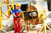 image of millwright  - builder man working with shovel during concrete cement solution mortar preparation in mixer at construction site - JPG