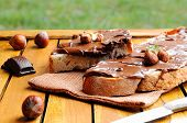 foto of hazelnut  - Two slices of bread with chocolate cream and hazelnuts on a wooden table outdoors - JPG