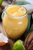foto of lime  - Homemade lime curd in glass jar with fresh limes and egg shells on old wooden background - JPG
