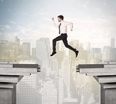 image of gap  - Energetic business man jumping over a bridge with gap concept - JPG