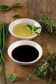 foto of vinegar  - Olive oil balsamic vinegar and herbs on vintage wooden background - JPG