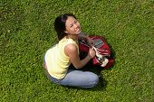 Female Student Sitting On Grass With Backpack Looking Up poster