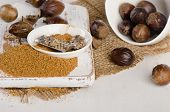 foto of ground nut  - Organic ground Nutmeg on a white wooden cutting board - JPG