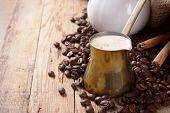 stock photo of cinnamon sticks  - Old coffee pot with coffee beans and cinnamon sticks on wooden rustic background - JPG