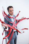 foto of trap  - Businessman trapped by red tape on white background - JPG