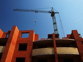 foto of construction crane  - Multistory building from brick under construction with no roof and construction crane - JPG