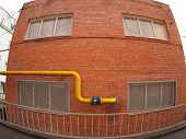 stock photo of gas-pipes  - Wall of a building with a yellow gas pipe and windows with wide angle fisheye view - JPG