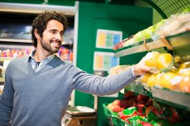 picture of grocery cart  - Smiling young man picking up vegetables in a grocery store - JPG