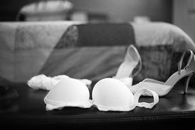 stock photo of garter-belt  - Wedding bridal garter belt bra lingerie and white shoes in Madrid Spain. Black and white photo with shallow depth of focus. ** Note: Shallow depth of field - JPG