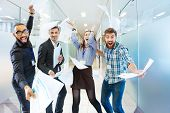 Group of joyful excited business people throwing papers and having fun in office poster