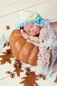 Tale Of Cinderella. Little Beautiful Newborn Baby Girl In A Bonnet Sleeping On A Pumpkin poster