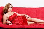 stock photo of futon  - Sexy woman lying on red sofa - JPG