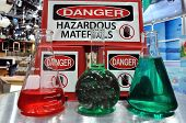 picture of pyrex  - Hazardous Sign with colored laboratory flasks in the foreground - JPG