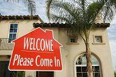 Bienvenido, por favor venga en bienes raíces muestra con nuevo hogar en el fondo.