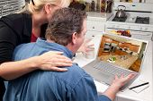 Couple In Kitchen Using Laptop to Research Home Improvement Ideas. Screen image can easily be replac
