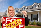 Beautiful Female Holding Keys to a New House & Sold Real Estate Sign.