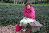 A senior woman shivering in the cold, alone on a park bench.