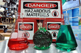 image of pyrex  - Hazardous Sign with colored laboratory flasks in the foreground - JPG