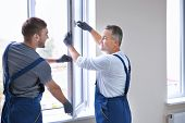 Construction worker with trainee installing window in house poster