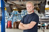 picture of car repair shop  - Portrait of cheerful young mechanic with arms crossed standing in his auto repair shop - JPG