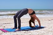 pic of dhanurasana  - an athletic brown haired woman is doing yoga exercise full wheel pose or Urdhva Dhanurasana also known as upward bow posture on an empty beach - JPG