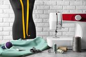 Tailoring items and sewing machine on table indoors poster