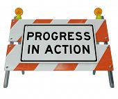 A road barrier reading Progress in Action signifies that work is being done on a project to lead to
