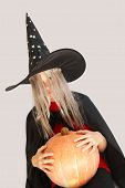 foto of jack-o-laterns-jack-o-latern  - Young blond girl dresses in hallowwen witch costume - JPG