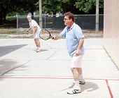 Two men - one senior and one mid-adult - playing racquetball outdoors.