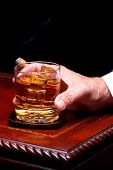 Mans Hand Holding Whiskey Glass and Cigar on wood & Leather Table Top