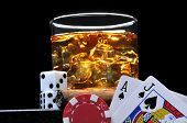 Glass of Whiskey with Dice, Cards and Poker Chip on Black Background