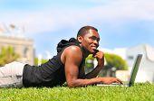 Africano-americano macho com laptop deitado na grama num cenário de Parque - azul céu e fora de foco bu