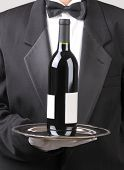 Close up of a Waiter holding red wine bottle on silver tray vertical format torso only