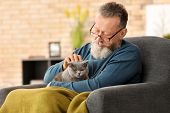 Senior man holding cute cat at home poster