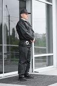 Male security guard standing outdoors poster
