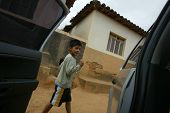 NOVO CRUZEIRO, BRAZIL - JULY 27: An unidentified child walks past a vehicle on July 27, 2005 in Novo
