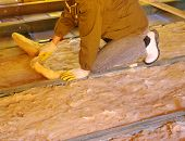 foto of insulator  - Construction worker thermally insulating house attic with glass wool - JPG