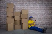 Brazilian Mailman Using A Smartphone In Front Of A Lot Of Packages In A Deposit poster