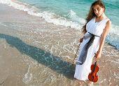 Junge attraktive Frau mit Violine auf Meer Hintergrund