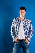 handsome young man with plaid shirt denim jeans in blue background